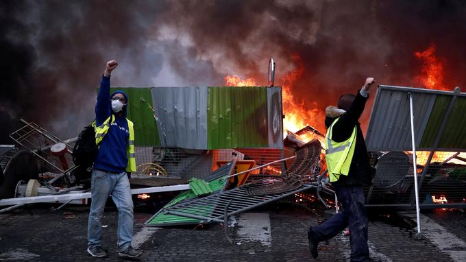 Protesters wearing yellow vests, a symbol of a French drivers' protest against higher fuel prices, shout out slogans during riots on the Champs-Elysees in Paris